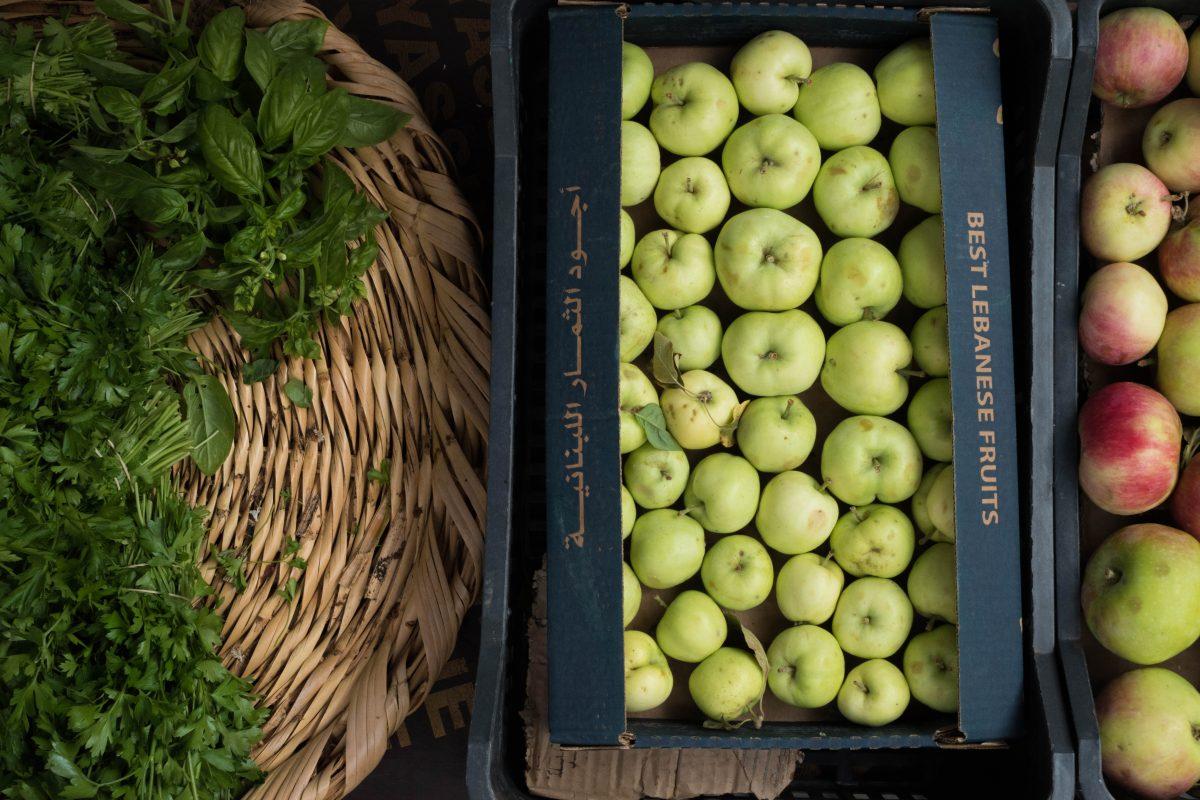 Kiste mit Äpfeln und Basilikum